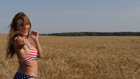 Follow me. Young beautiful girl in an American bikini walking on a wheat field