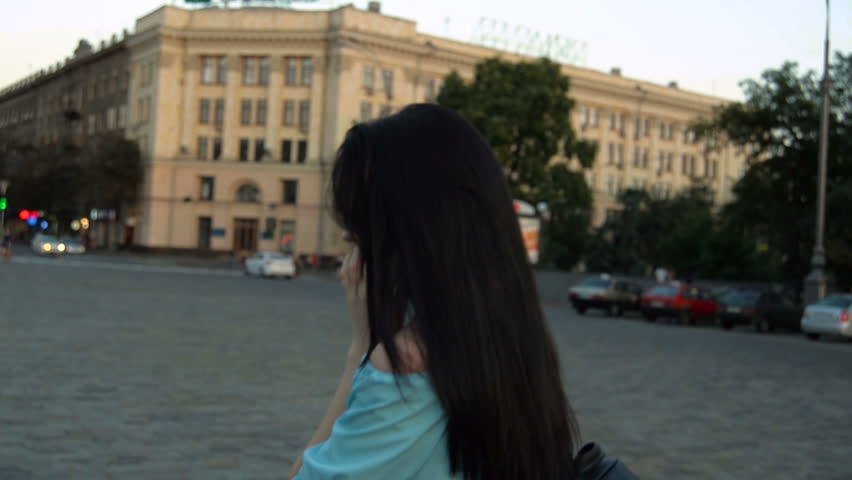 Young brunette haired walking down the street in the evening and said by telephone   Shutterstock HD Video #30791314