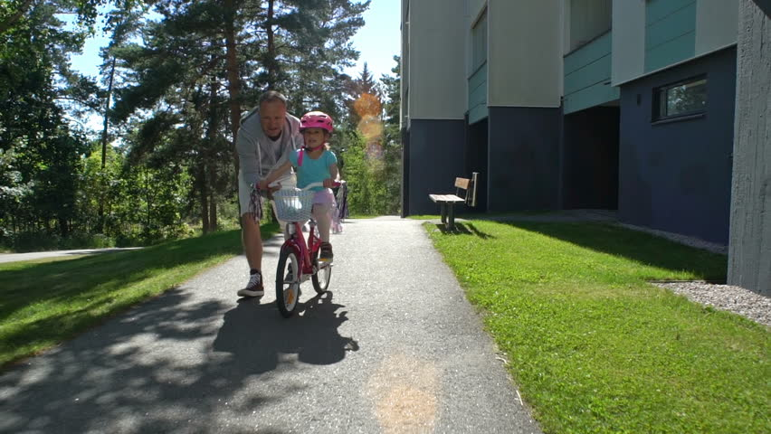 First cycling. Dad teaches his daughter to ride a bike. Slow Motion.