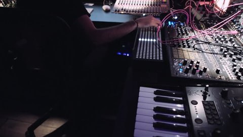 Camera moves above many sound production panels in professional studio with musician workind on sound check and mixing and recordings new mixtape