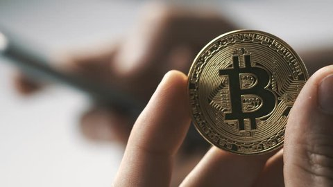 Using a smartphone with a hand and holding a bitcoin coin with the other. Bitcoin is a worldwide cryptocurrency and digital payment system.