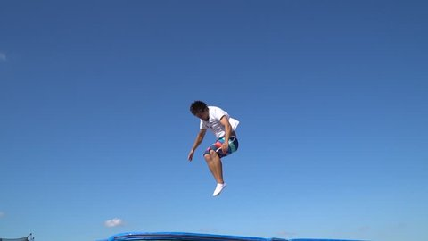 Adult man in beach shorts shows acrobatic stunts on a trampoline, slow motion