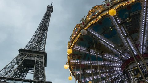 Time lapse of Eiffel Tower, symbol of Paris and iconic landmark in France, and illuminated merry-go-round at night. Famous touristic place and romantic travel destination in Europe. Tourism and travel