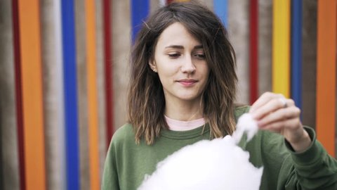 Close up of a young woman with dark hair eating cotton candy while standing outside against a colored wall with wooden planks. Handheld real time close up shot