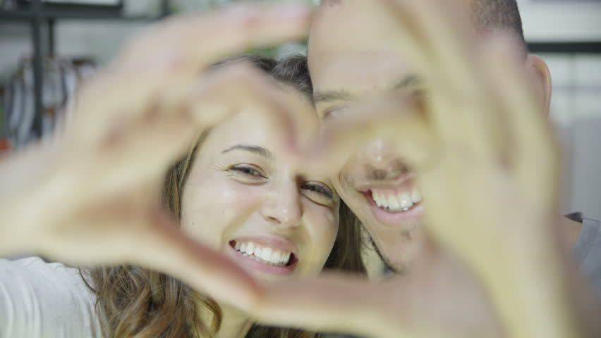 Close up of an attractive young mixed ethnicity couple who are laughing and making a heart shape with their hands. In slow motion.