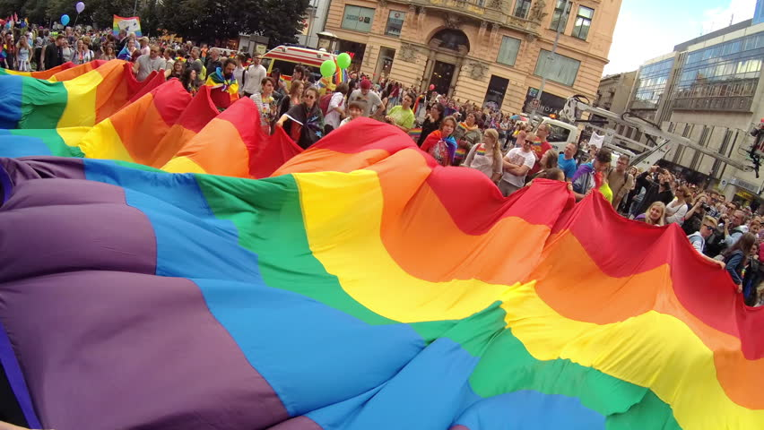 PRAGUE, CZECH REPUBLIC AUGUST 12, 2017: GLBT guys and girls wave rainbow flag at Gay Pride parade. Cheerful girls smiling and waving their hands at camera. Symbol of gay, lesbian, bisexual community.