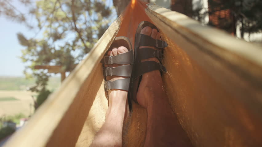 Man chilling out and lying in hammock and swinging, male feet in leather slippers enjoying in house backyard