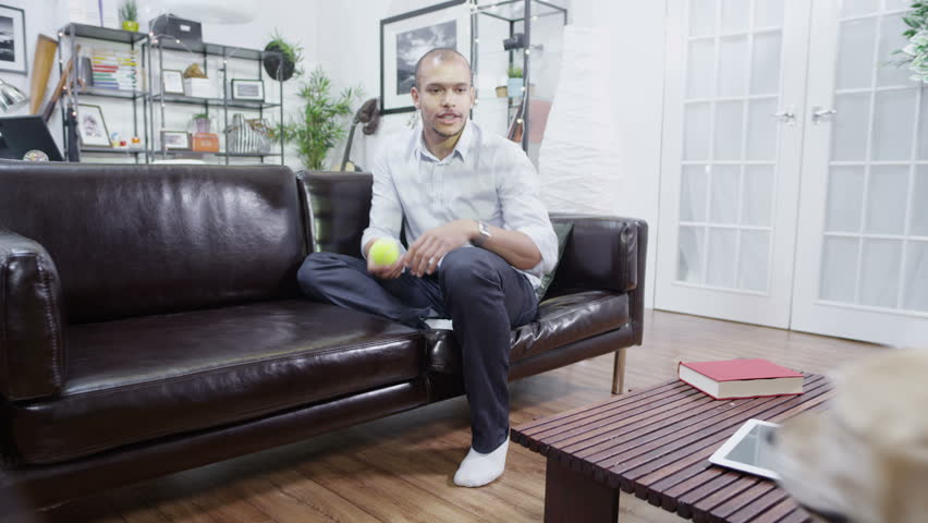 Man relaxing at home throws ball for his dog to catch