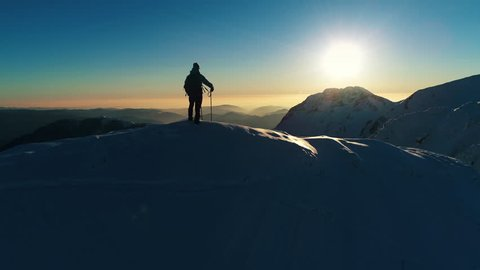 Aerial - Adult male mountaineer standing on top of snowy mountain top and holding his hand on his forehead, looking into the distance