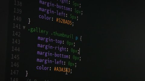 Programmer scrolling up and down and checking code for editing futuristic technology concept with grain and dark tone processed