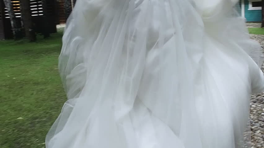 Stock video of elegant wedding dress hanging from flowering ...