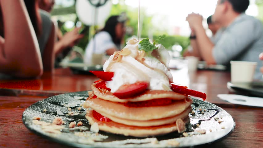 4K Maple syrup being poured over warm stacked pancakes with fruit, Auto focus.
