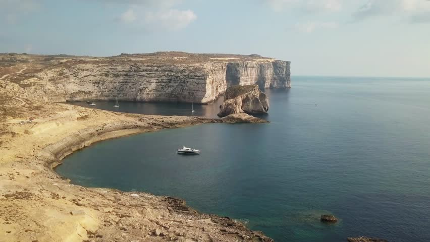 Aerial view of dramatic ocean coastline of Gozo, Malta. Shot from above flying over boats and bay in Mediterranean island. 4k drone footage of cliffs and sea landscape for Europe vacation and travel.