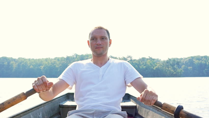 Serious focused concentrated young fit man rowing boat on lake in Virginia during summer in white shirt | Shutterstock HD Video #30897211