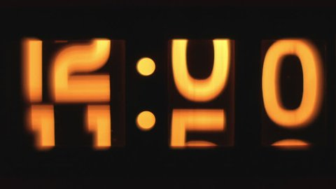 stop motion of an old style flip clock lit up and passing through 12 hours