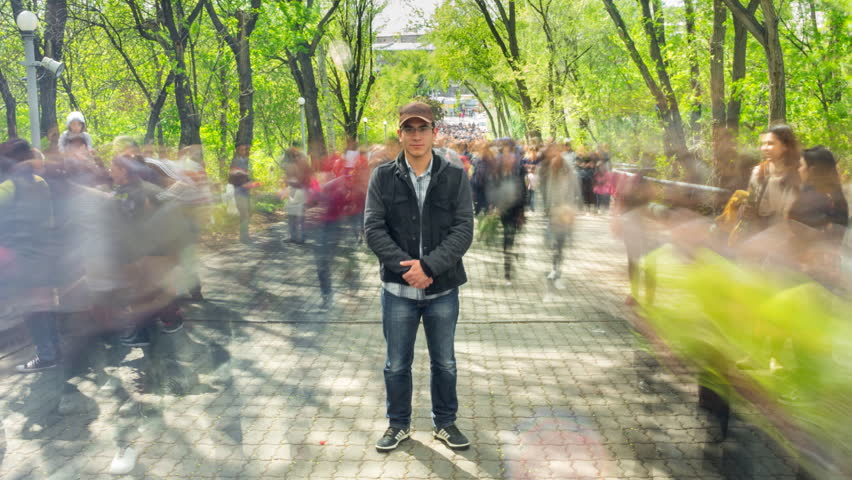 Man standing alone in blurred crowd, on background green trees. Time Laps. The camera is approaching. Full HD