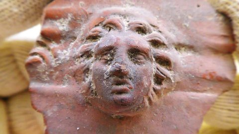 Archeologist inspects authentic ancient Roman Greek Clay figure of Gorgon Medusa, a winged human female with living venomous snakes in place of hair. Gazers upon her hideous face would turn to stone.