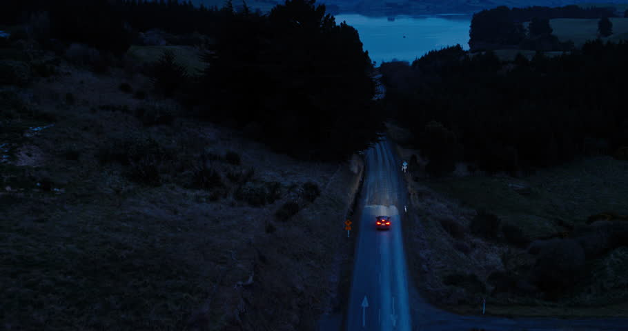 Aerial view car driving on country road at dusk through dark forest with headlights   Shutterstock HD Video #30913942