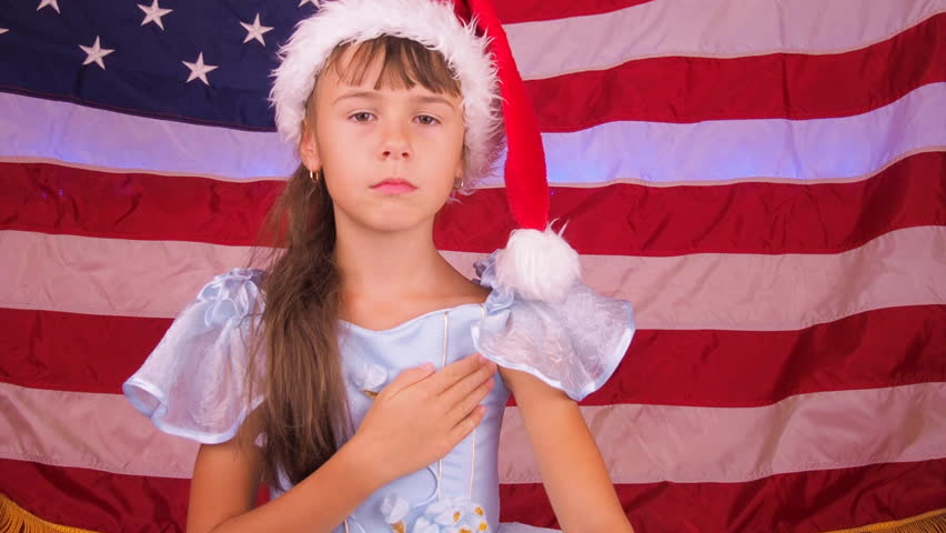 Serious American girl in the background of the US flag. A little girl listens to the US hymn in the Santa Claus hat.