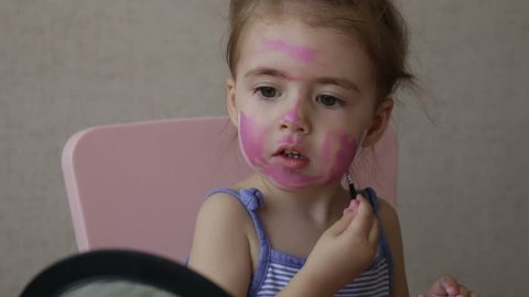 blonde three years old baby painting color stripes on her face looking at mirror