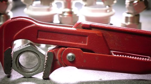 Red metalwork adjustable spanner for sanitary works against the background of Water shutoff and connecting shutoff valves for water supply