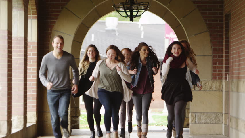 Group of young adults running towards the camera together.