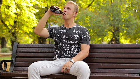 Alcoholism in a public place. A drunk man drinks beer in a park on a bench