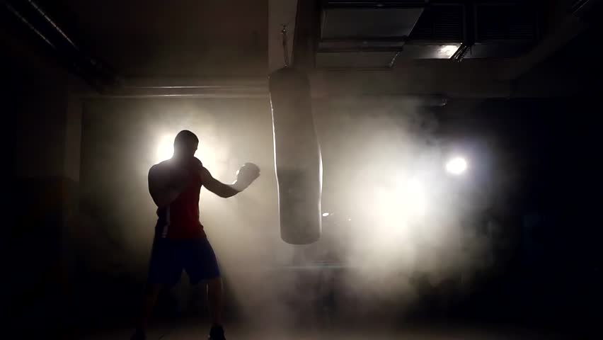 Alone large boxer is working out blows on a punching bag in a dark gym | Shutterstock HD Video #30958360