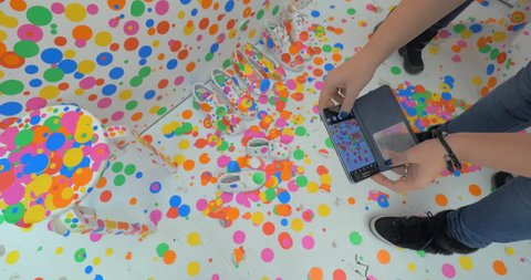 HELSINKI, FINLAND - JANUARY 07, 2017: Visitor making mobile photo of colorful shoes in Obliteration Room. Exhibition in Infinity by Yayoi Kusama, famous Japanese artist