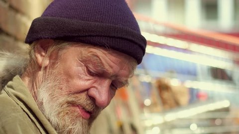 Close up view of old homeless man eating from metal bowl. Old man living in the street taking meal.