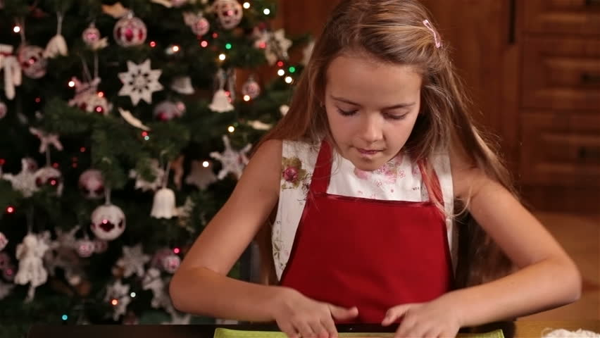 little girl cutting christmas cookie shapes from a gingerbread dough camera tilt down