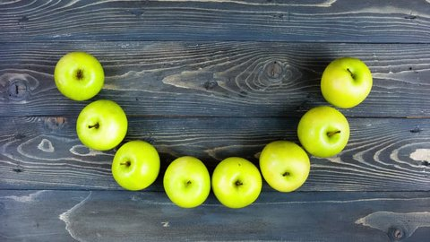 Time lapse loop animation of apple smile. Stop motion fresh fruits on wooden table, 4K. Concept for dentistry, fitness, healthy eating