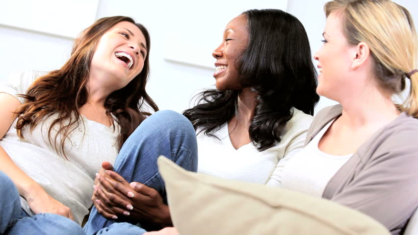 Multi ethnic girls gossiping on couch in modern home