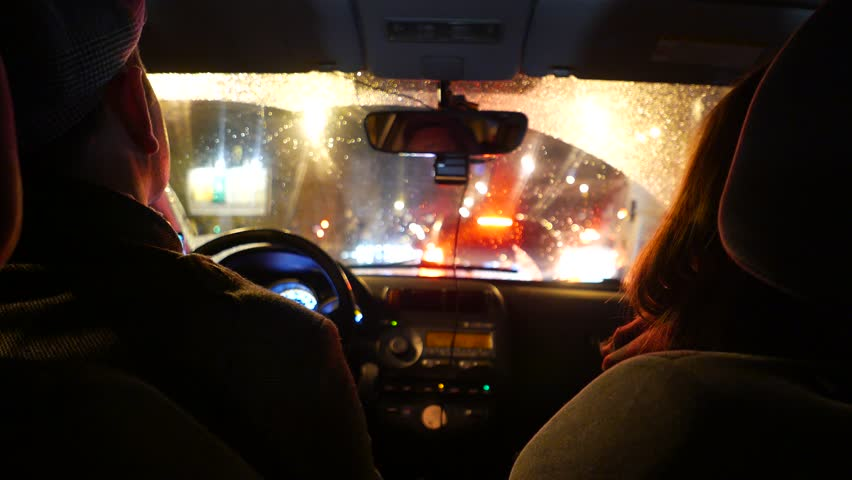 Couple ride car in slow night traffic, rainy weather, blurred vehicles  lights seen outdoors through wet glass of wind-screen, POV camera at rear  seat.