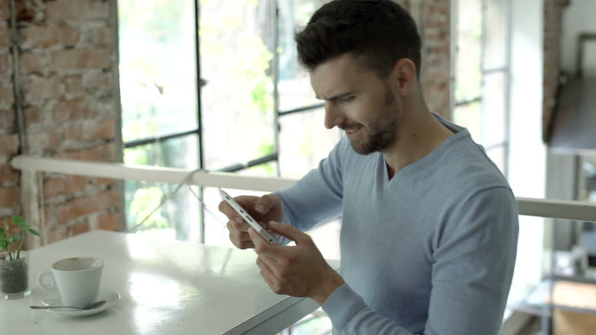 Handsome man looks excited while playing game on smartphone, steadycam shot  | Shutterstock HD Video #30992263