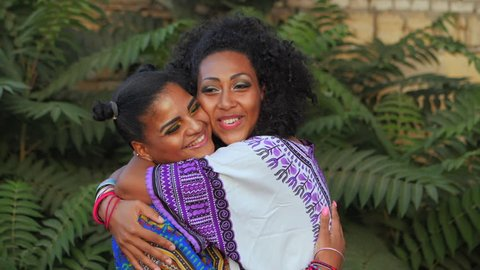 Two happy beautiful afro-american women friends hugging outdoor in park. Multi ethnic girls wearing colorful clothing enjoys the meeting and laughing in slow motion. Dolly shot.