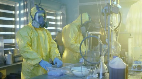 In the Underground Laboratory Two Clandestine Chemists Wearing Protective Masks and Coveralls Pack Bags Full of Crystal Meth into Boxes. Equipment. They Squat in an Abandoned Building. 4K UHD.