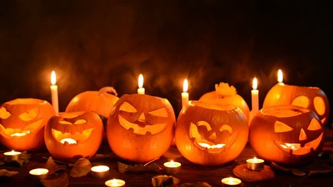 Halloween pumpkins with candles over dark background, closeup, front view, locked down video