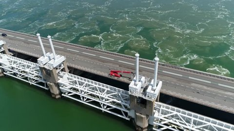 Aerial Eastern Scheldt storm surge barrier Oosterscheldekering flying over panning down showing traffic driving over largest of 13 Delta Works series of dams and storm surge barriers Zeeland Holland