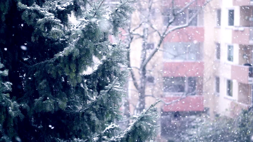 Falling snow at appartment blocks in a city, slow motion