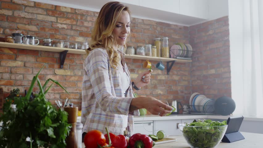 Woman listening music while cooking | Shutterstock HD Video #31048993