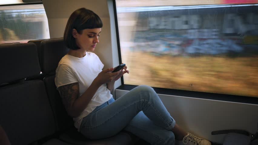 Cute young millennial hipster woman or teenager with cool arm tattoos sits in fast train, next to window, landscapes pass by, she uses smartphone and texts smiling and chuckling | Shutterstock HD Video #31052023