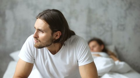 Thoughtful worried man sitting on the side of bed with sleeping woman at background, doubtful upset husband thinking of breaking up divorce, feeling unsure frustrated obsessed about family problem