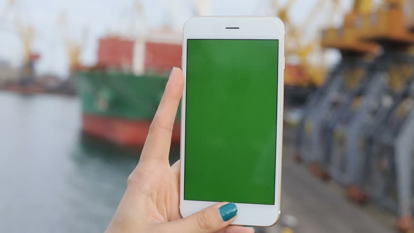 Woman hand holding using mobile smart phone blank green screen chromakey port ship sea vacation traveling trip closeup unfocused background tapping touching display networking gadget digital point