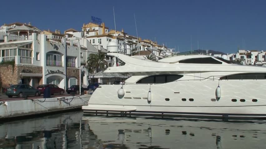 Panning shot of large white expensive yachts in Puerto Banus port in Spain on the Costa del Sol