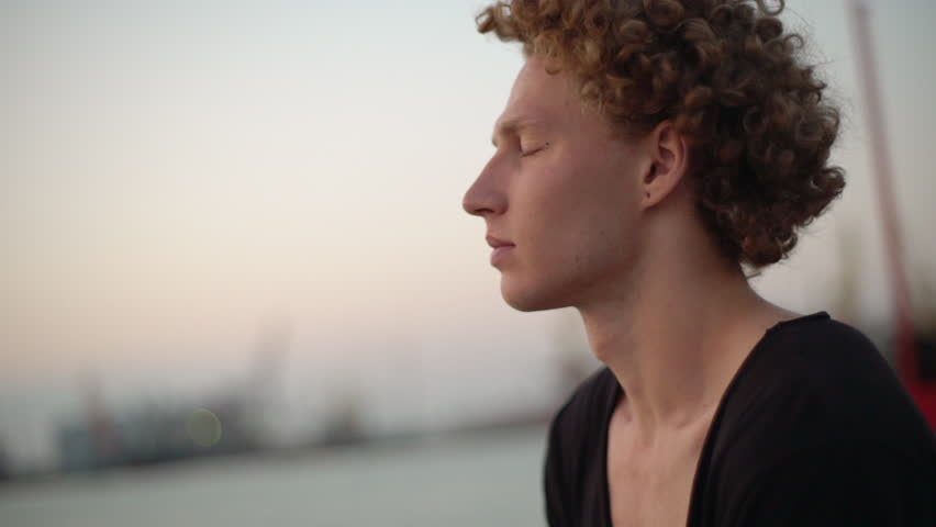 White male with red curly hair looking at the sea, black shirt. Slow motion