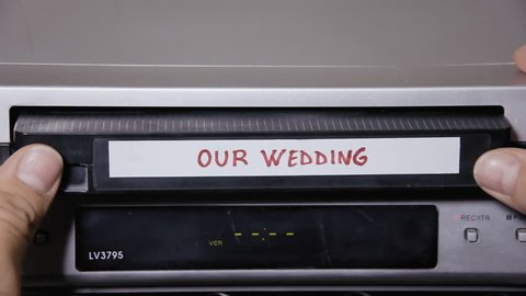 Inserting and removing a VHS tape from a VCR. The title says Our wedding.