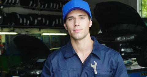 In a car repair garage a mechanic after settling the car shows the keys as a car's ready to start. Concept of: security, safety, insurance, keys of the future, assistance and customer care.