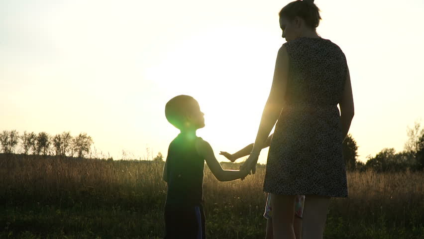 Mother plays with son and daughter at field at sunset. Slow mo | Shutterstock HD Video #31094983