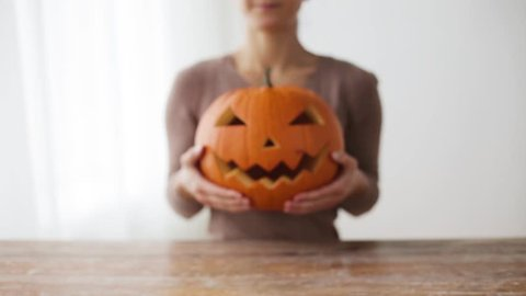 halloween, decoration and holidays concept - close up of woman with carved pumpkin or jack-o-lantern at home